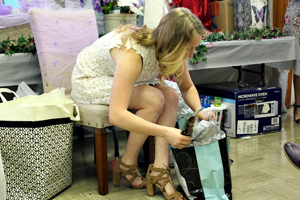 bride opening gifts at rustic themed bridal shower
