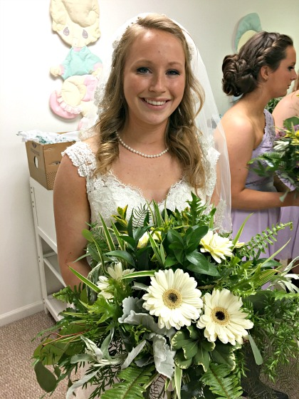 Bride with bouquet of daisies and greenery