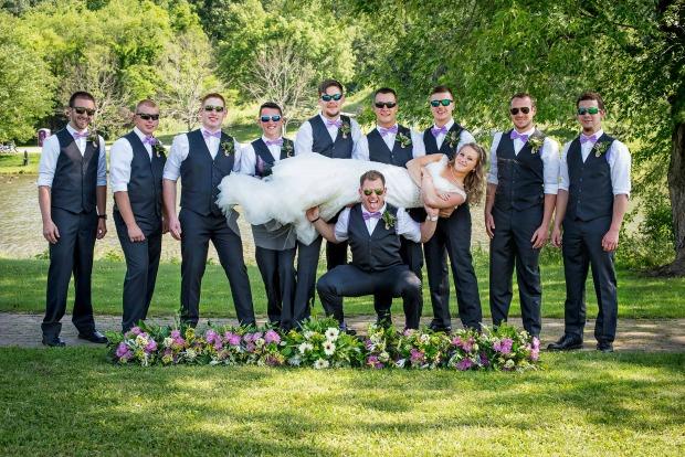 Groomsmen holding bride