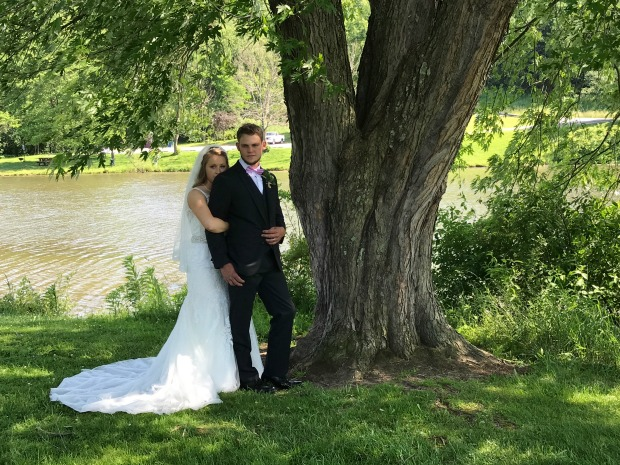 Wedding pictures in park by water and trees