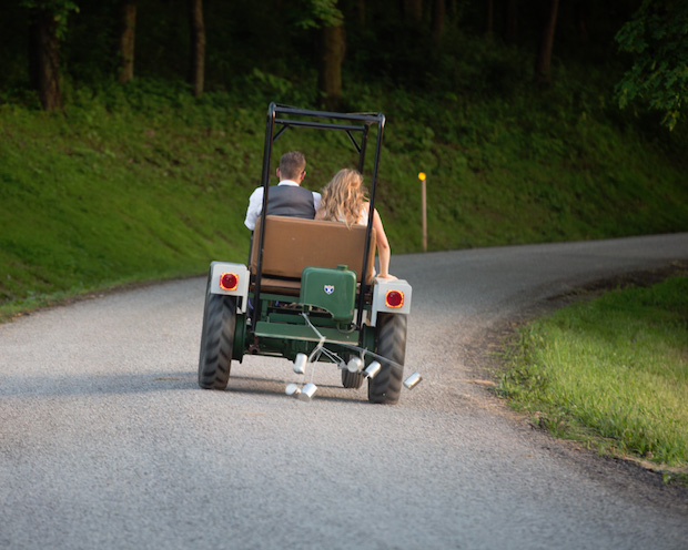 Bride and groom driving away in a tractor