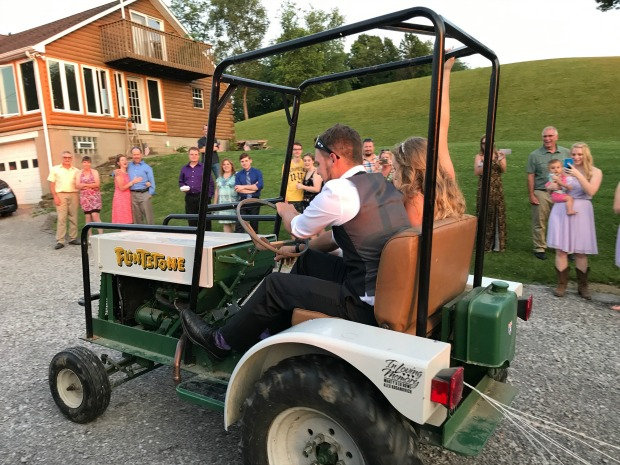 Bride and groom driving away in tractor
