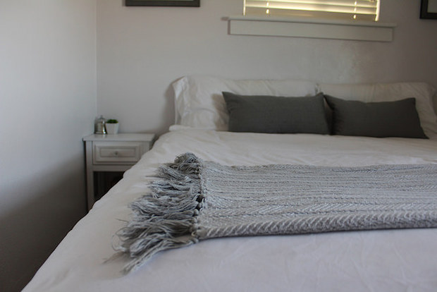 Gray and white blanket with tassels