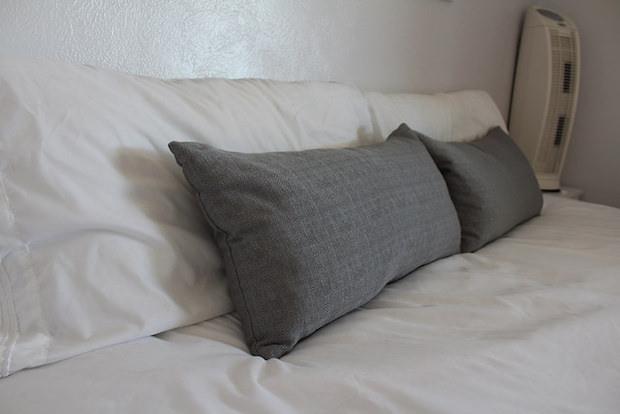 Gray throw pillows on white bed