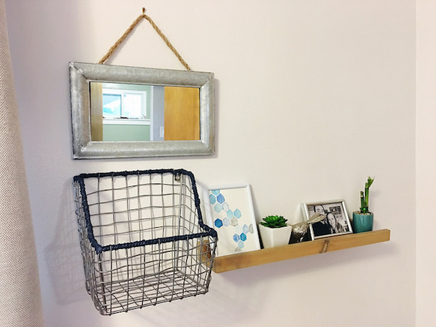 Industrial gallery wall with galvanized mirror, wooden picture ledge, wire basket, and blue and gray accents