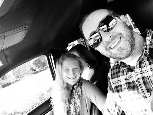 Husband and wife black and white picture smiling in car