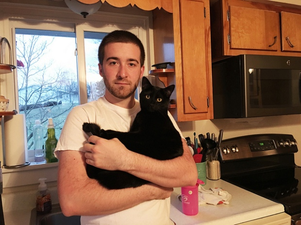 Guy holding black cat