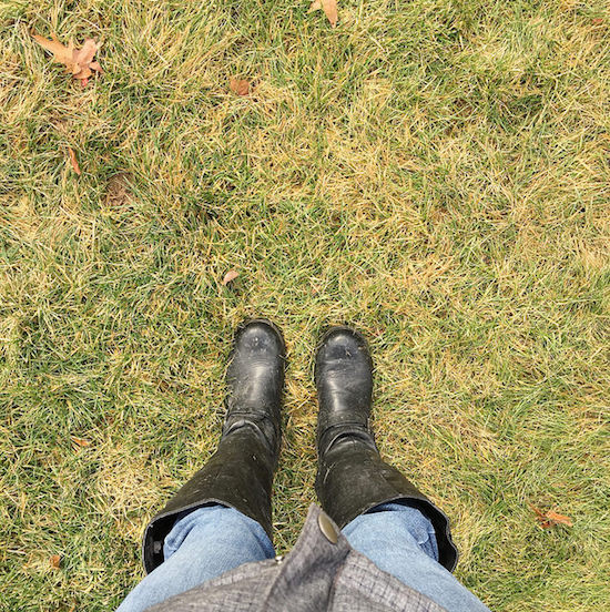 Black boots on green grass in January