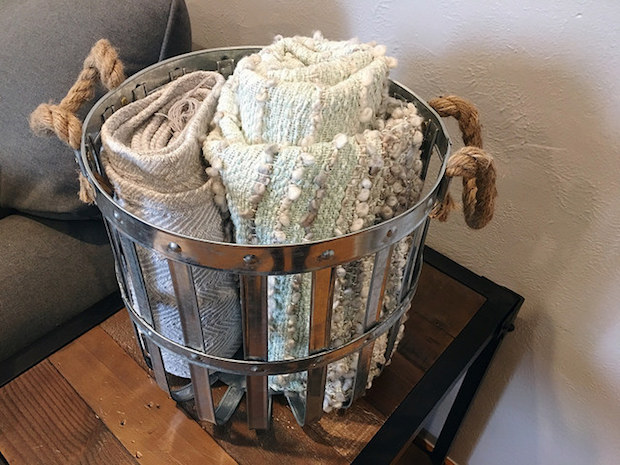 Gray and blue blankets with tassels in galvanized metal basket with rope handles industrial