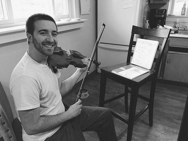 Guy practicing violin in kitchen