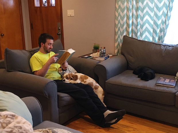 Guy reading book with cocker spaniel in lap