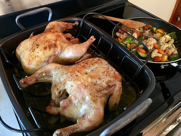 Two roasted rotisserie chickens with sautéed vegetables