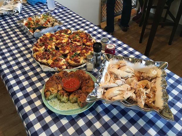 Table with chicken, parmesan bread, twice baked potatoes, horseradish, beet horseradish, and sautéed vegetables