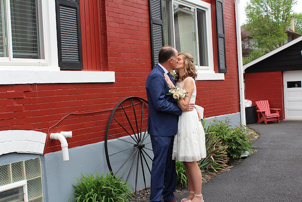 Wedding picture of couple kissing in front of red house and big wheel
