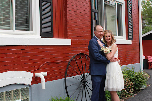 Couple smiling for wedding picture in front of red house and black wheel in Pittsburgh