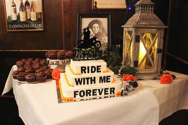 Harley Davidson Wedding Cake that says ride with me forever with motorcycle wedding cake topper and orange and black