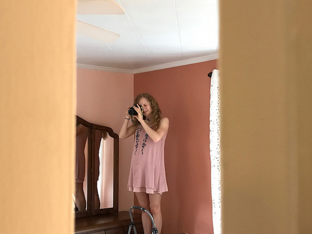 Girl taking pictures inside a house with DSLR camera