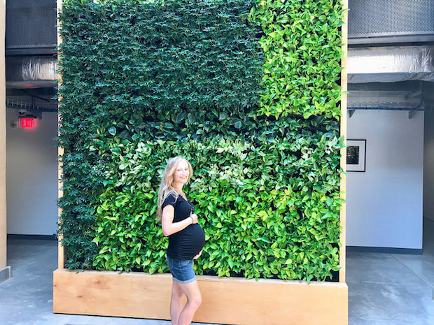 Pregnant girl in front of living plant wall at Eden Hall Chatham University