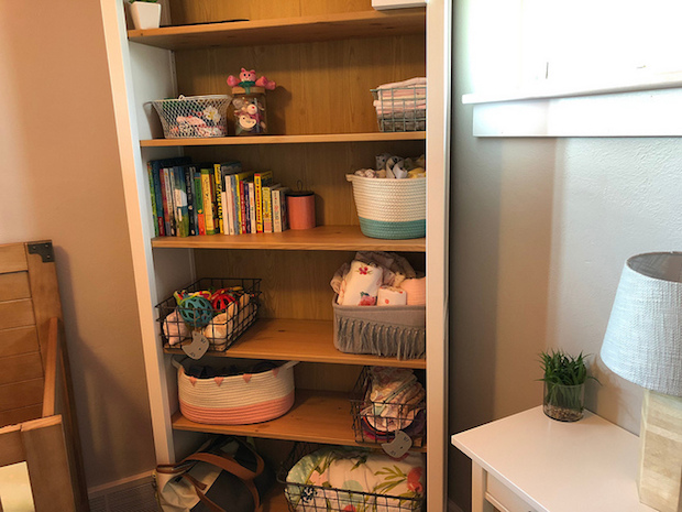 Baby girl nursery bookshelf from Ikea with fabric and steel baskets