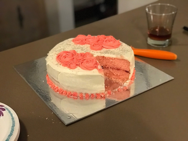 Strawberry cake with vanilla buttercream decorated with roses and sprinkles