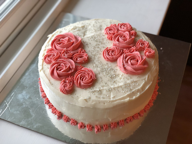 Strawberry cake with vanilla buttercream and rosettes with silver sprinkles