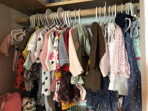 Baby girl closet with clothes and wood bars