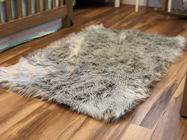 Fuzzy gray Nicole Miller rug on wood floor