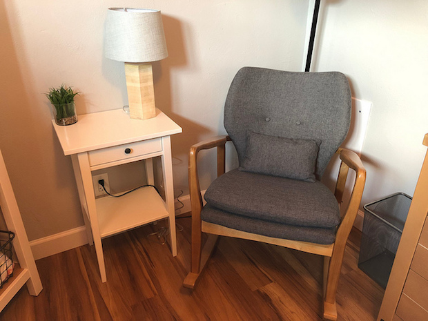 Gray rocking chair and white side table in baby girl nursery