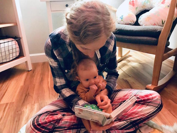 Girl reading to baby