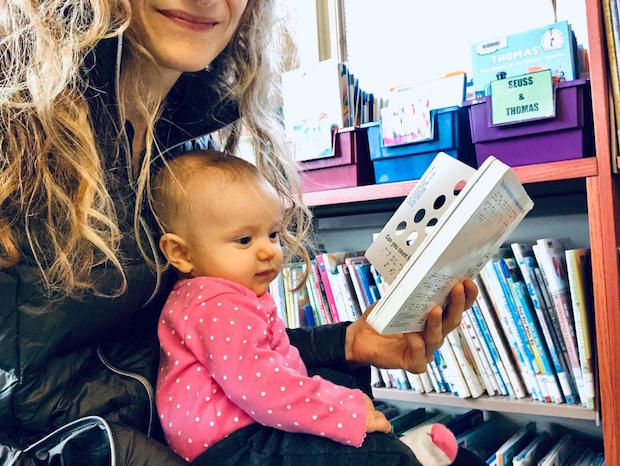 Baby reading book at library