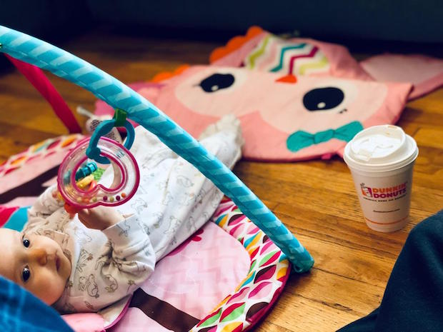 Baby on play mat with Dunkin Donuts coffee