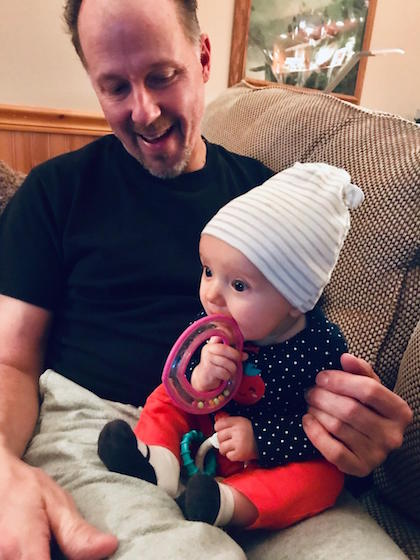 Baby girl in hat sitting on grandfather's lap