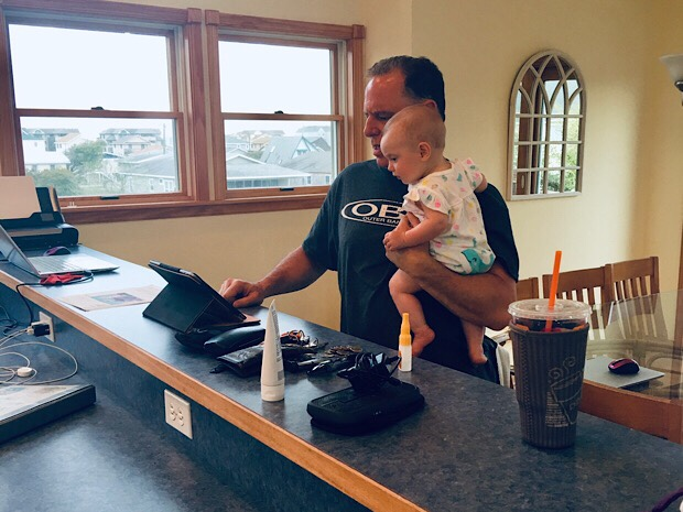 Grandfather holding baby girl and looking at computer