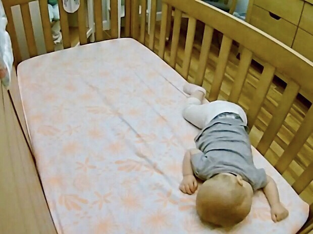 Baby sleeping in crib with leg out of crib slat