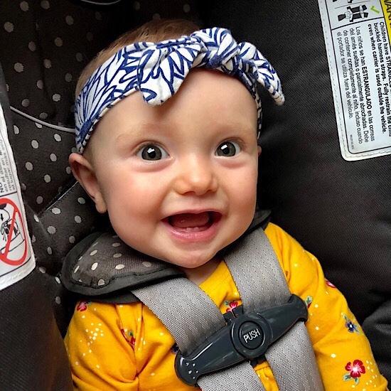 Baby with headband bow smiling in carseat