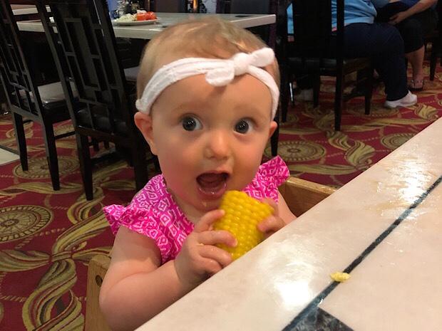 Baby girl eating cob of corn at restaurant