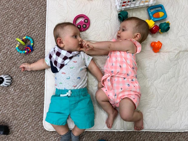 Baby boy and girl playing on play mat