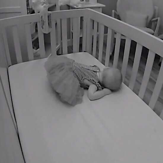Baby girl sleeping in crib with butt in the air