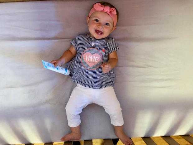 Baby girl nine months old laying in crib and smiling with headband and diaper rash cream