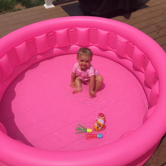 Baby girl sitting in pink swimming pool