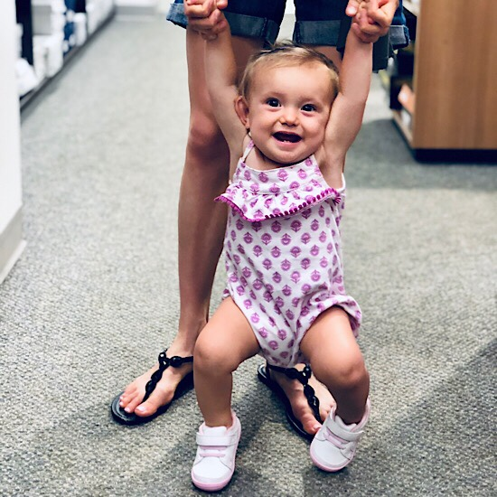 Baby girl smiling in shoe store