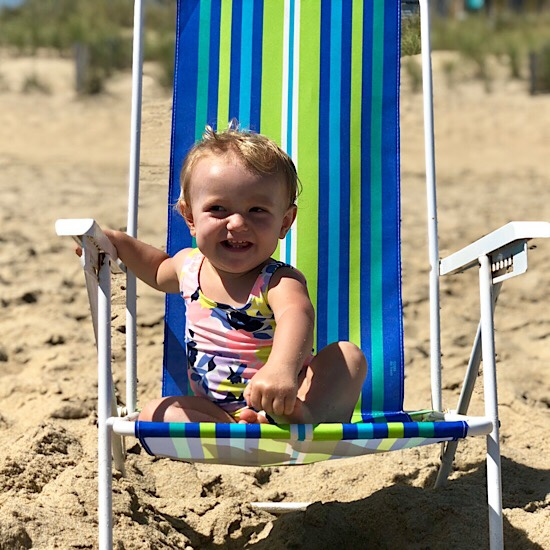 Baby girl sitting in beach chair on the beach