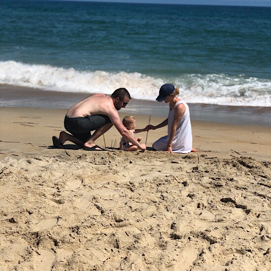 Mom and dad building sandcastle with baby