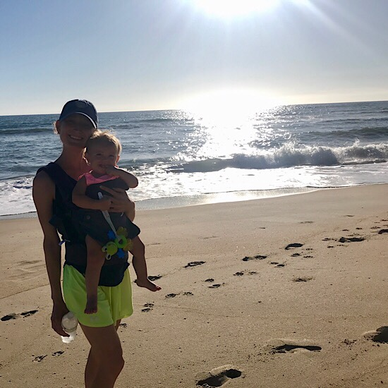 Girl wearing baby in carrier on the beach in Outer Banks by the ocean