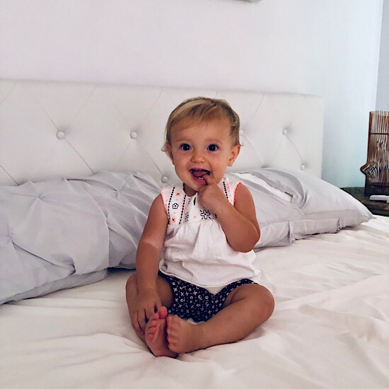 Baby girl sitting on bed smiling
