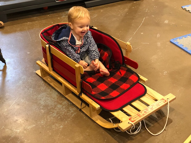 Baby girl sitting in LL Bean sled