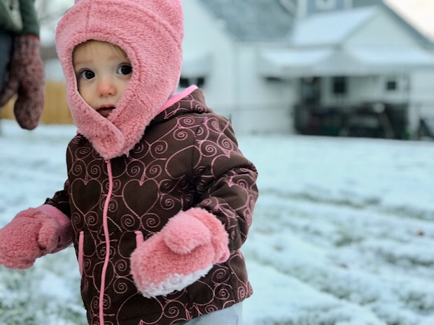 Baby girl in pink hat in the snow