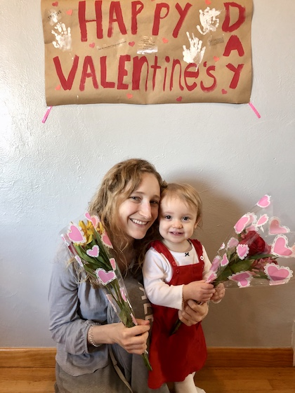 Mom and daughter with Valentines Day sign and flowers