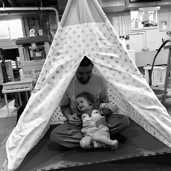 Father and daughter playing in teepee