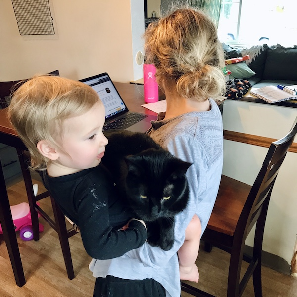 Mom holding baby and cat